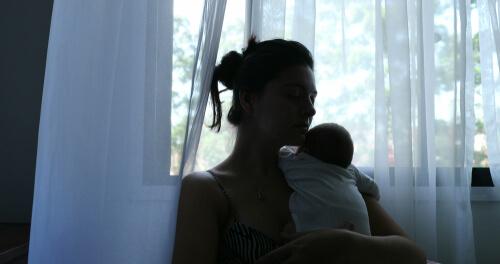 Woman With Newborn Near Window