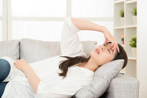 Woman With Terrible Headache On A Sofa