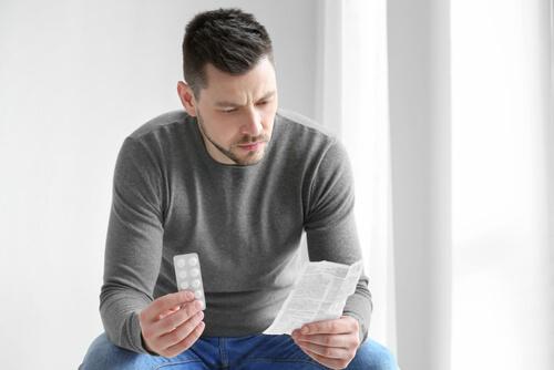 Man Reading Package Insert For The Drug
