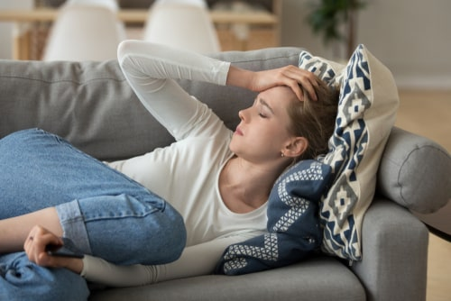Woman lying at home on couch.