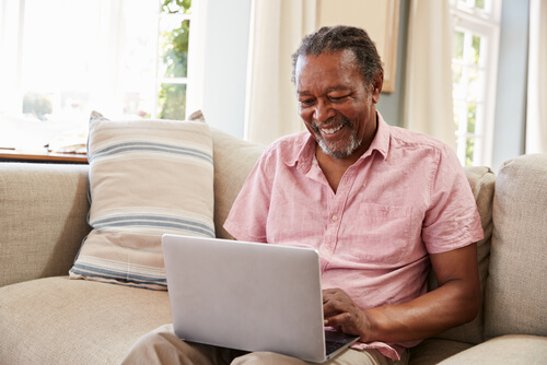 Senior Man Sitting On Sofa Using Laptop.