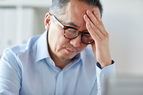 Man With A Headache Holds His Head