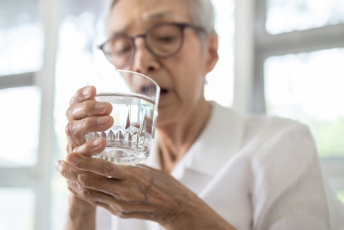 Senior woman with tremor holding a glass.
