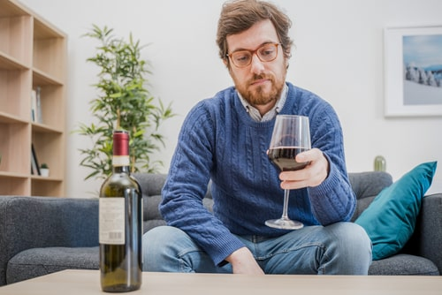 Depressed man with alcohol drink.