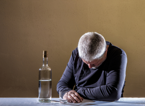 Man sits at a table with a bottle of alcohol.