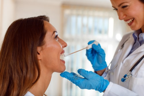 woman doctor takes a mouth swab.