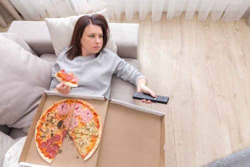 Depressed woman eating pizza.