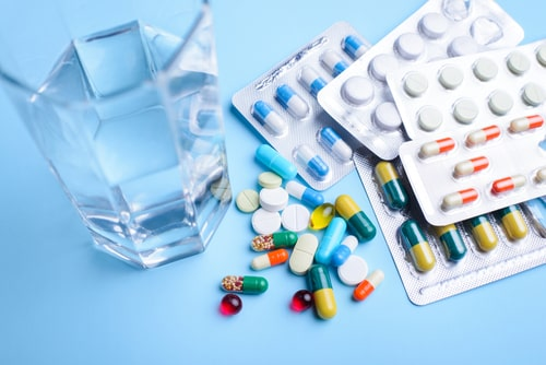 Colorful tablets with capsules near glass of water.