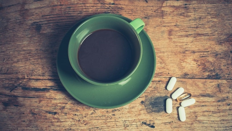 A cup of black coffee with six pills of adderall.