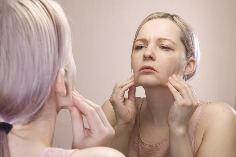 Girl with problematic skin looking in the mirror.