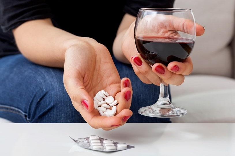 Woman drinks wine with vicodin.