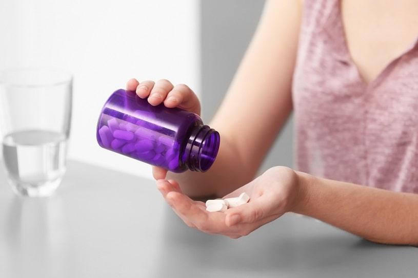 Taking pills from purple bottle.