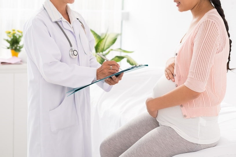 Pregnant woman consulting a doctor.