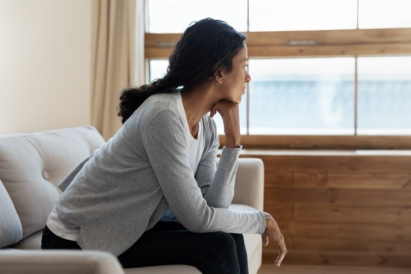 Depressed woman sits on the couch.