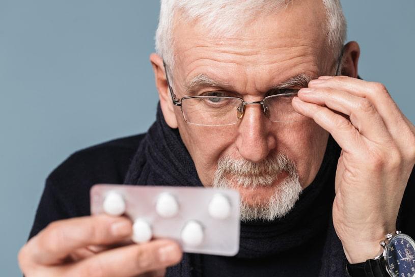 Senior man looking at his pills.
