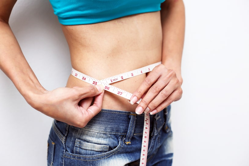 Woman measuring waistline with measure tape.