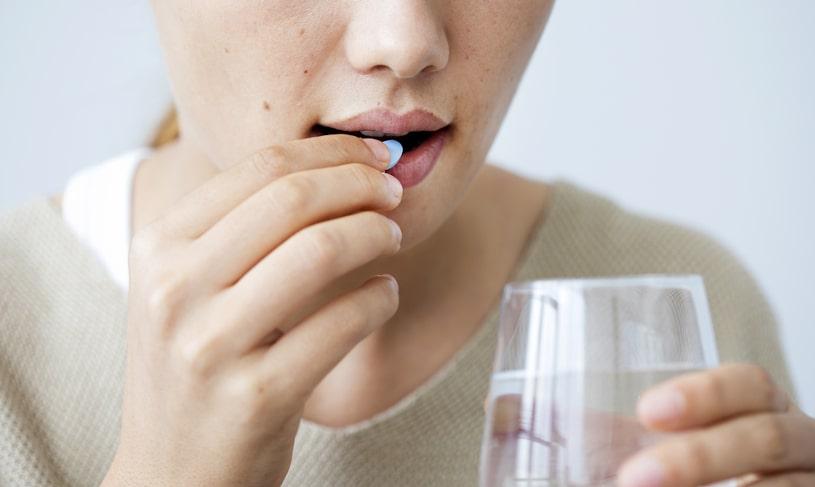 Young woman taking zoloft pill.