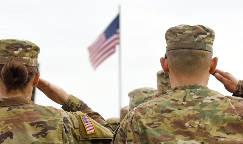 American soldiers saluting the US flag.