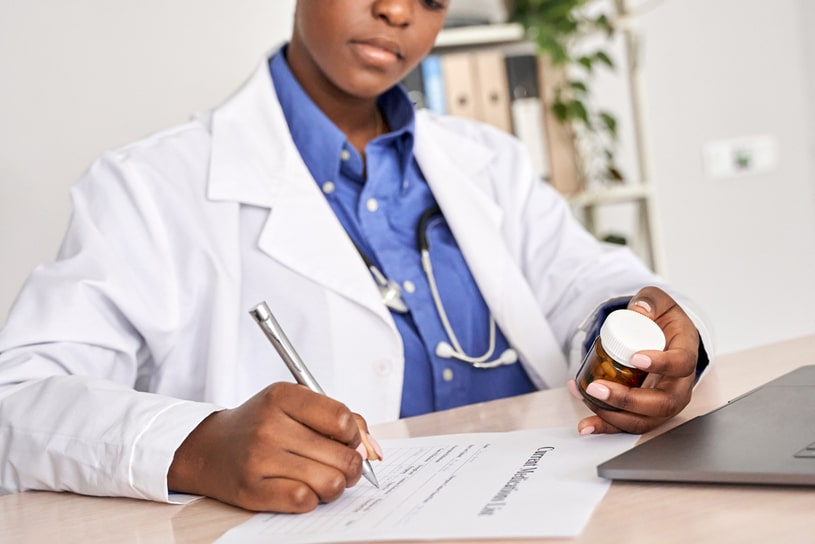 The doctor prescribes medicine and holds it in her hands.