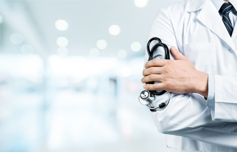 A stethoscope in the hand of a doctor in a white coat.