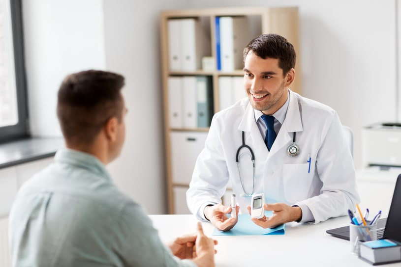 A kind doctor talks to a patient in a light office.