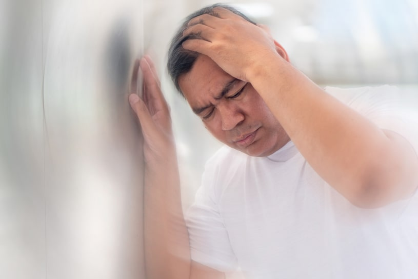 A middle-aged man feels dizzy while holding onto a wall with his hand.
