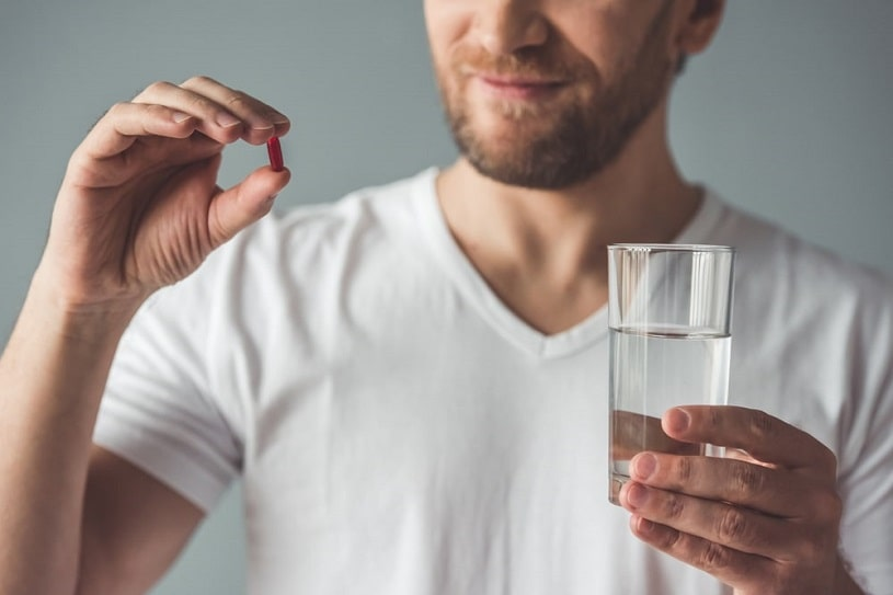Man holding Vicodin pill.