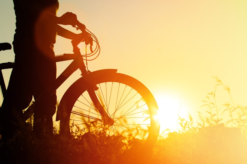 A man with a bicycle during sunset.