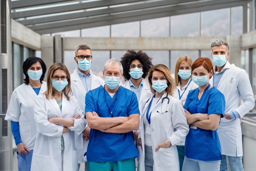 A team of doctors stands in the center of the room.