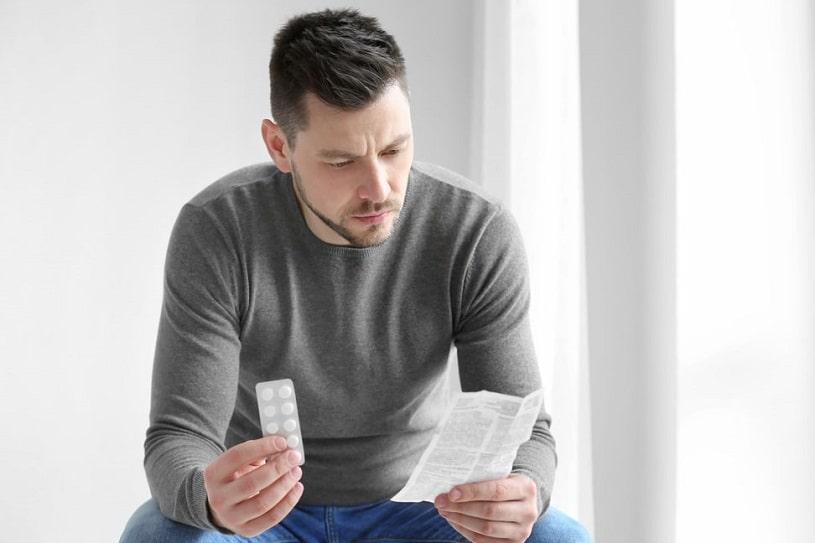 Man reading pill instructions.
