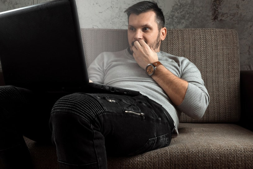 A man watches an adult video on a laptop.