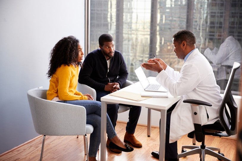 Couple Having Consultation With Male Doctor.