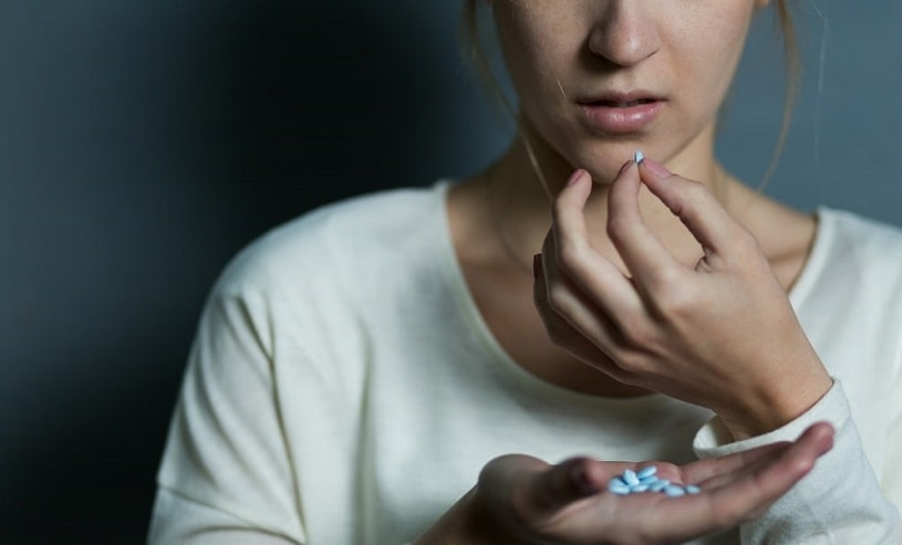Depressed girl takes a lot of Xanax pills.