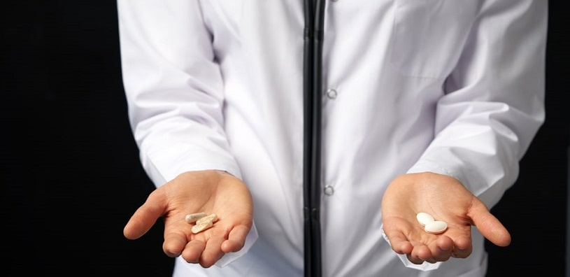 Doctor holding in hands norco and percocet Pills.