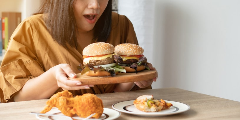 Hungry overweight woman holding hamburger.