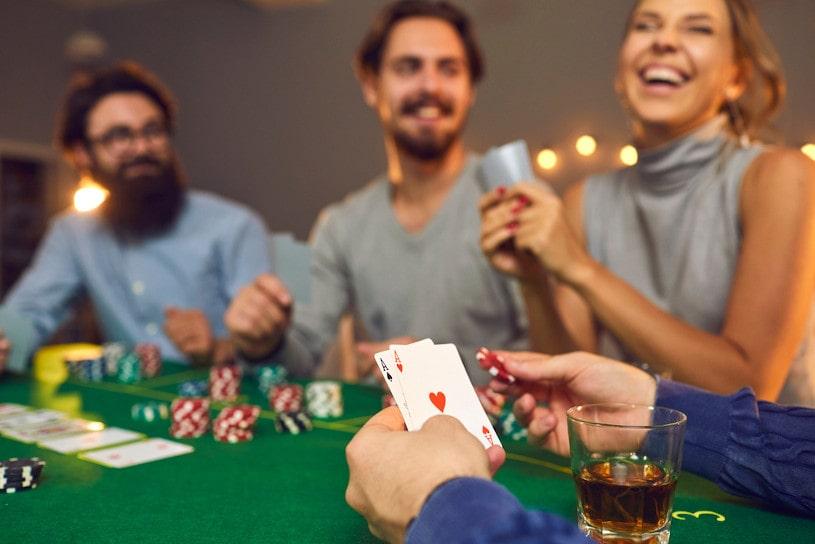 Mans hands holding poker cards.