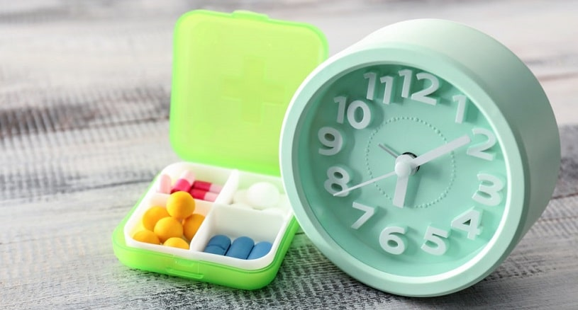 Plastic container with pills and clock on wooden table.