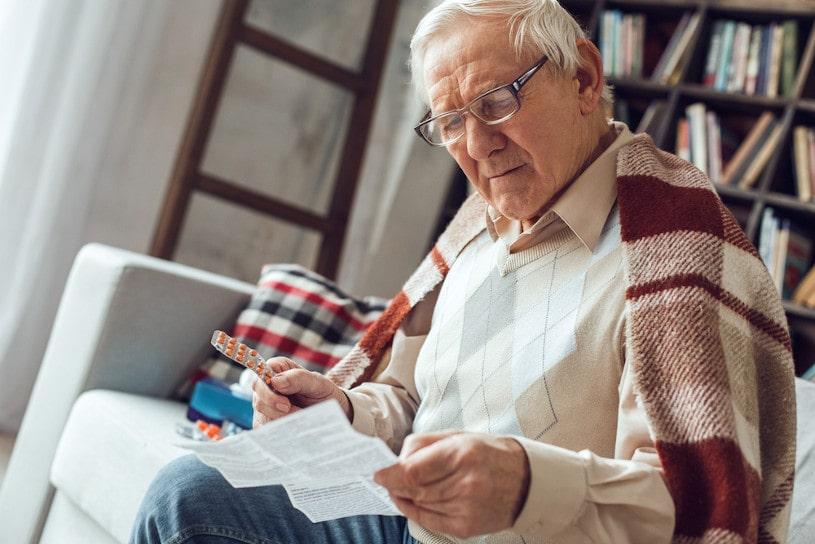 Senior man alone sitting on sofa reading instructiion.