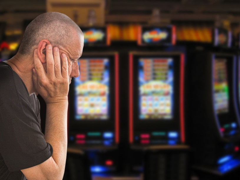 depressed caucasian man sitting in front of casino slots.