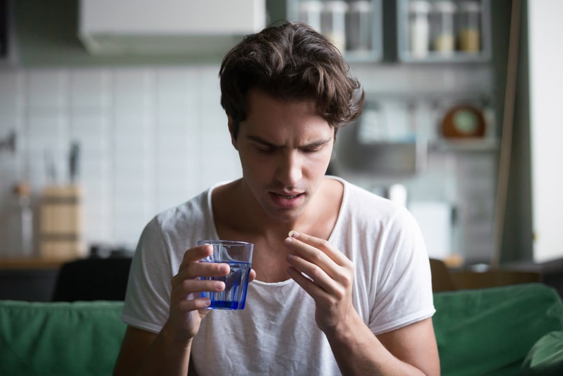 A young guy holds a pill to his mouth.
