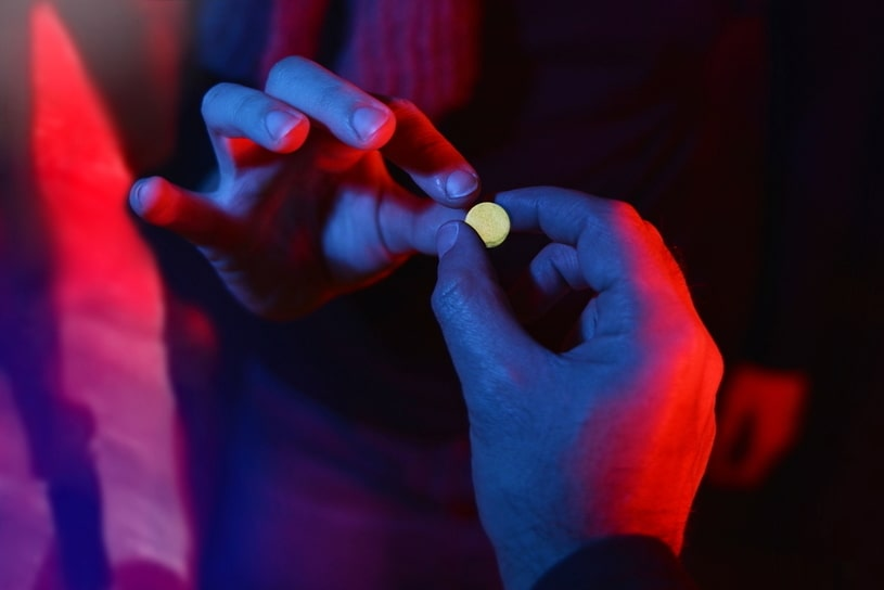 Hand takes a pill in a room with dark light.