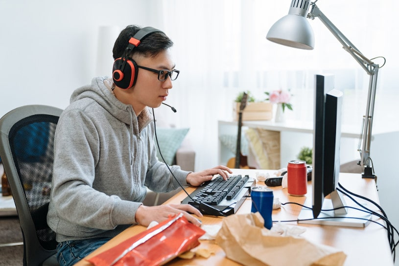 young asian man in headphones with pc computer.