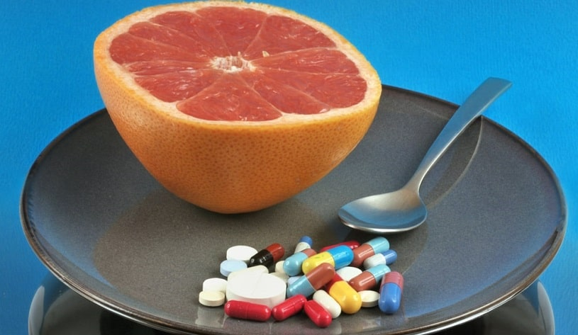 Half grapefruit in a plate with assorted medicines.