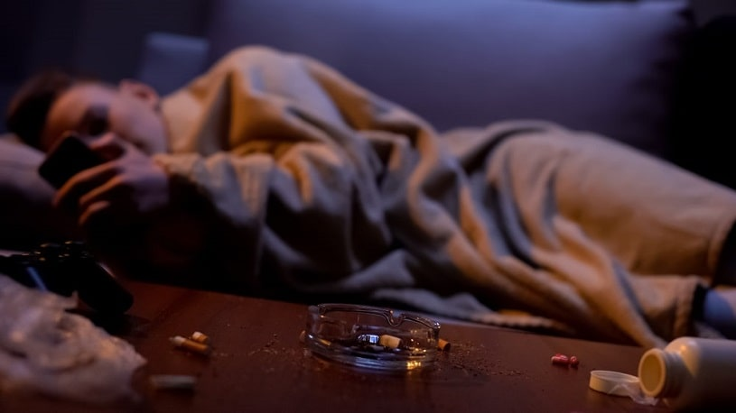 Nicotine addicted teenager covered with blanket.