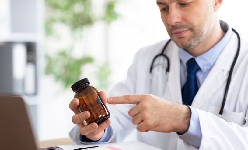 Doctor pointing at tablets in the bottle.