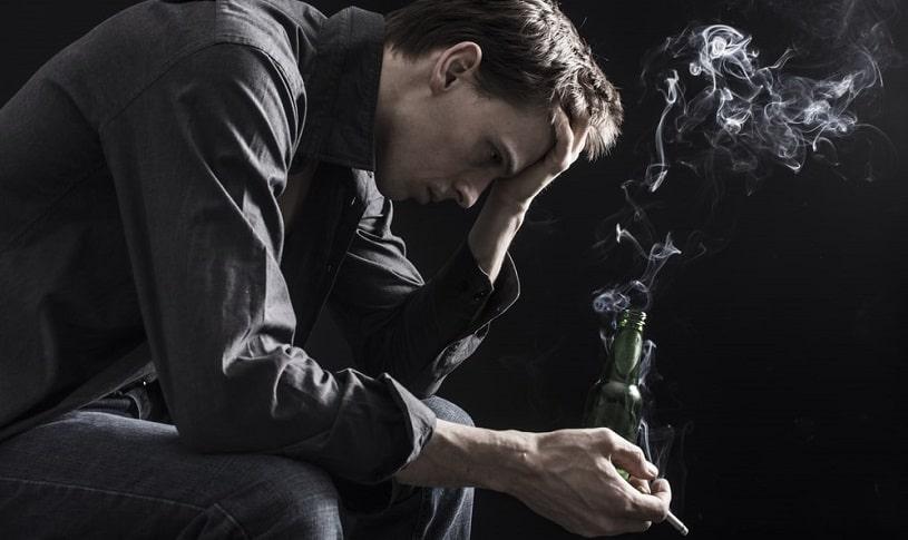 Depressed man smoking a cigarette.
