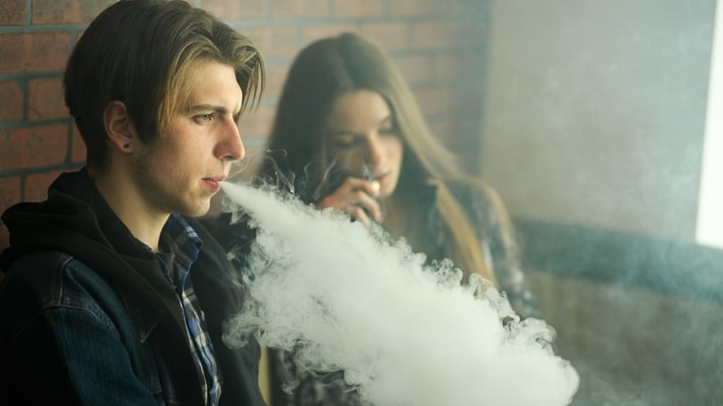 Young man vaping next to a girl.