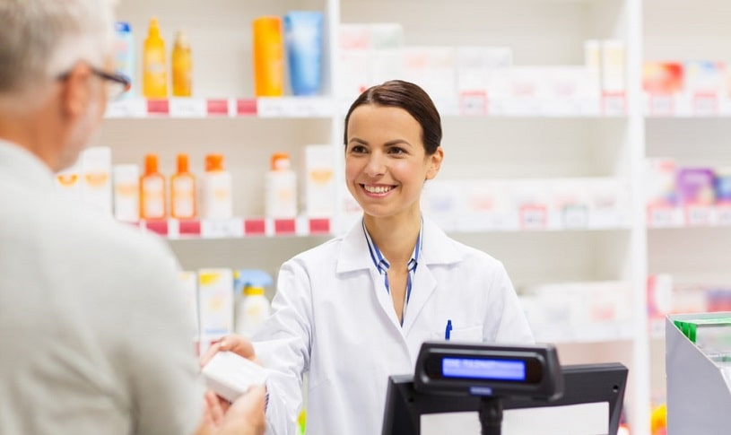 Pharmacist giving pills to a patient.