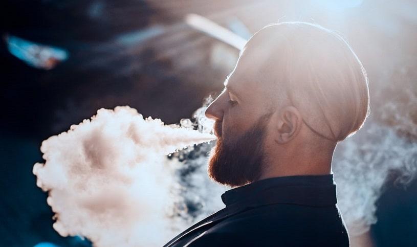Vaping man exhaling a lot of vapor.