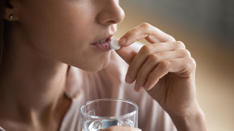 Woman with a glass of water in her hand takes an Ambien pill.